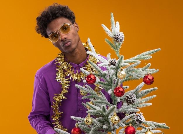 Zelfverzekerde jonge afro-amerikaanse man met bril met klatergoud slinger om nek staande achter versierde kerstboom met samengeknepen lippen geïsoleerd op oranje muur