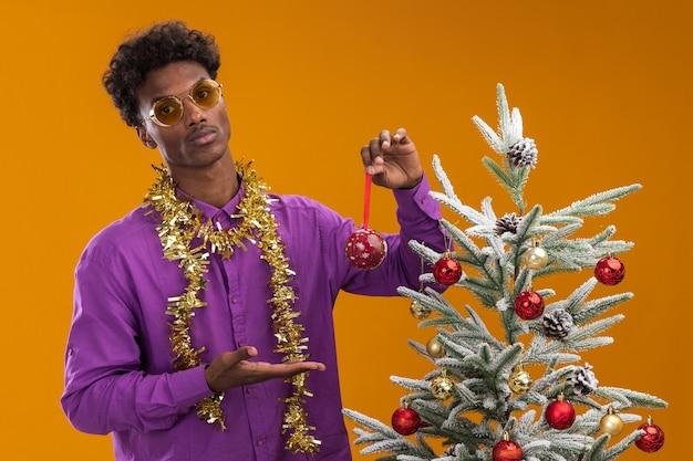 Zelfverzekerde jonge afro-amerikaanse man met bril met klatergoud slinger rond de nek staan ?? in de buurt van de kerstboom en versiert het met kerstballen