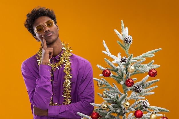 Zelfverzekerde jonge afro-amerikaanse man met bril met klatergoud slinger rond nek staande in de buurt van versierde kerstboom aanraken gezicht geïsoleerd op oranje muur