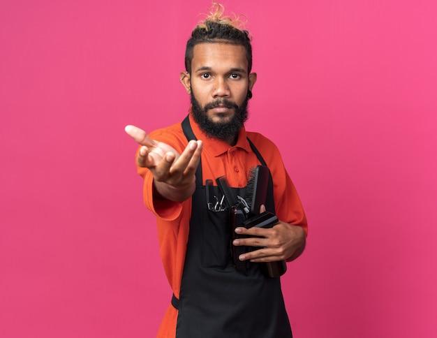 Zelfverzekerde jonge afro-amerikaanse mannelijke kapper met uniforme kappersgereedschappen die de hand uitstrekken naar de camera