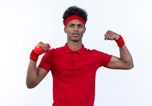 Zelfverzekerde jonge afro-amerikaanse sportieve man met haedband en polsbandje houdt bumbbell en doet sterk gebaar geïsoleerd op witte achtergrond