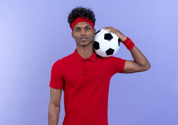 Zelfverzekerde jonge afro-amerikaanse sportieve man met hoofdband en polsband met bal op schouder