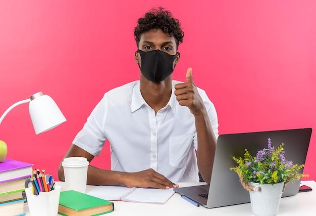 Zelfverzekerde jonge afro-amerikaanse student die een gezichtsmasker draagt dat aan het bureau zit met schoolhulpmiddelen die omhoog duimen