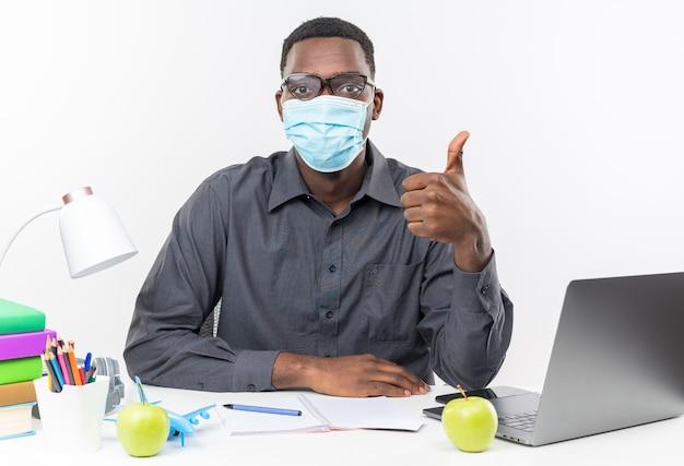 Zelfverzekerde jonge afro-amerikaanse student in optische bril met een medisch masker zittend aan een bureau met schoolhulpmiddelen die omhoog geïsoleerd op een witte muur duimen