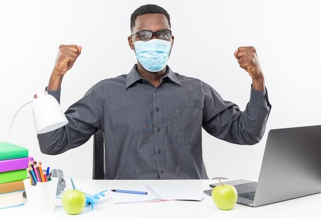 Zelfverzekerde jonge afro-amerikaanse student in optische bril met een medisch masker zittend aan een bureau met schoolhulpmiddelen die vuisten op een witte muur houden