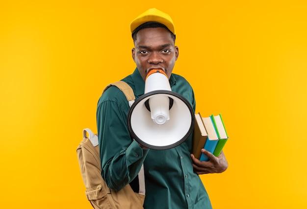 Zelfverzekerde jonge afro-amerikaanse student met pet en rugzak die boeken vasthoudt en in een luidspreker spreekt