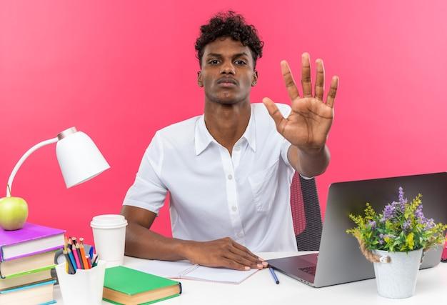 Zelfverzekerde jonge afro-amerikaanse student zit aan een bureau met schoolhulpmiddelen die een stophandteken gebaren