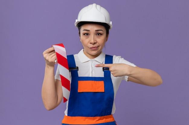 Zelfverzekerde jonge aziatische bouwvrouw met een witte veiligheidshelm die vasthoudt en wijst op waarschuwingstape