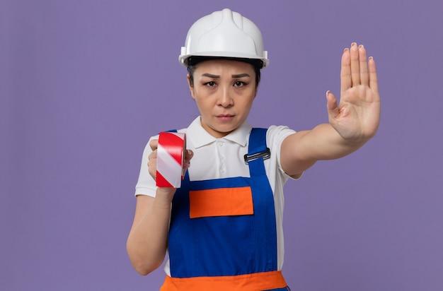 Zelfverzekerde jonge aziatische bouwvrouw met een witte veiligheidshelm die waarschuwingstape vasthoudt en een stopbord gebaren