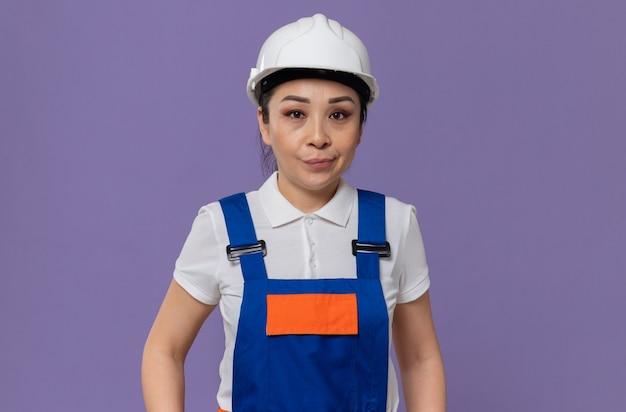 Zelfverzekerde jonge aziatische bouwvrouw met witte veiligheidshelm op zoek