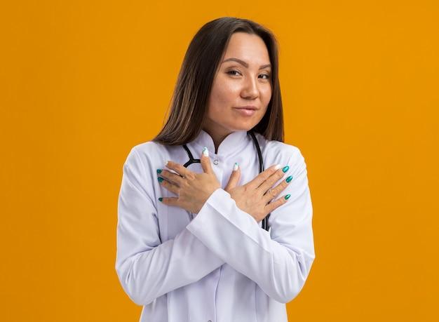Zelfverzekerde jonge aziatische vrouwelijke arts die medische mantel en stethoscoop draagt en naar de voorkant kijkt en de handen gekruist houdt op de borst geïsoleerd op een oranje muur met kopieerruimte