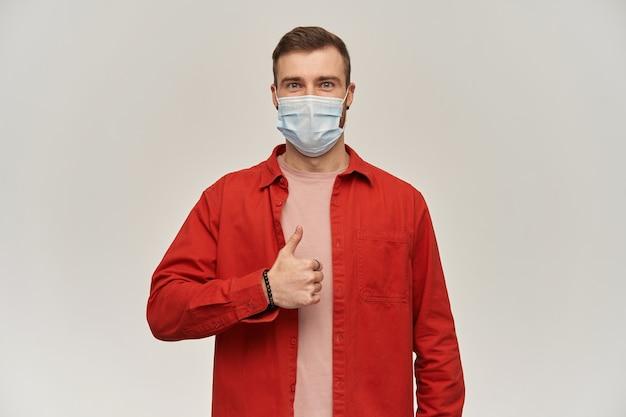 Zelfverzekerde jonge bebaarde man in rood shirt en virusbeschermend masker op gezicht tegen coronavirus staan en duimen opdagen over witte muur
