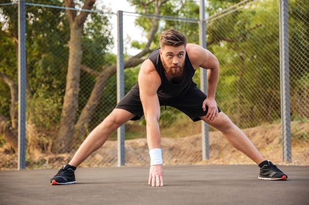Zelfverzekerde jonge, bebaarde mannelijke atleet die zich uitstrekt en opwarmt voordat hij buiten jogt