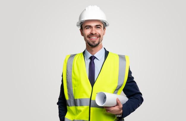 Zelfverzekerde jonge bebaarde mannelijke bouwingenieur in veiligheidshelm en vest over formeel pak gerolde blauwdruk te houden en te kijken met een glimlach
