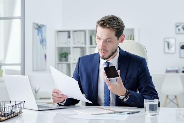 Zelfverzekerde jonge bebaarde zakenman in donkerblauw pak zittend aan een bureau en spraakbericht opnemen voor collega terwijl commentaar op contract
