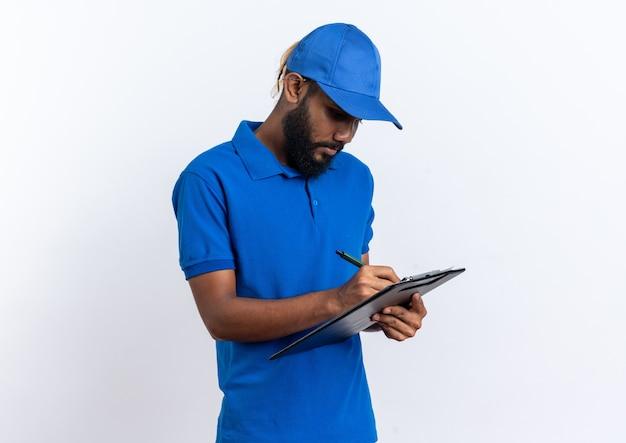 Zelfverzekerde jonge bezorger die iets schrijft op klembord geïsoleerd op een witte muur met kopieerruimte