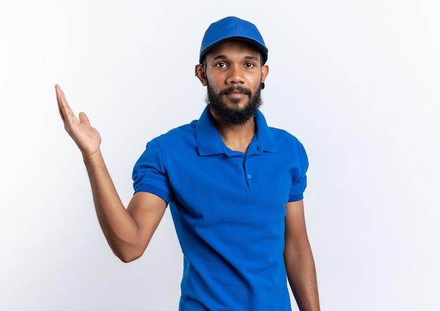 Zelfverzekerde jonge bezorger die met opgeheven hand staat geïsoleerd op een witte muur met kopieerruimte