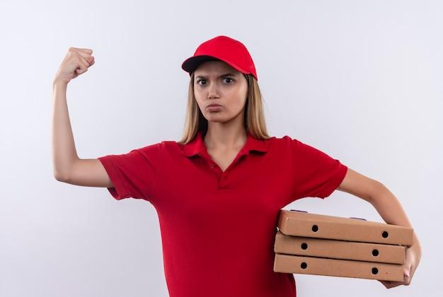 Zelfverzekerde jonge bezorger die rode uniform en pet draagt die pizzadozen houdt en sterk gebaar doet