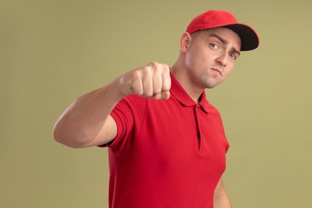 Zelfverzekerde jonge bezorger die uniform en pet draagt die vuist naar camera houdt die op olijfgroene muur wordt geïsoleerd