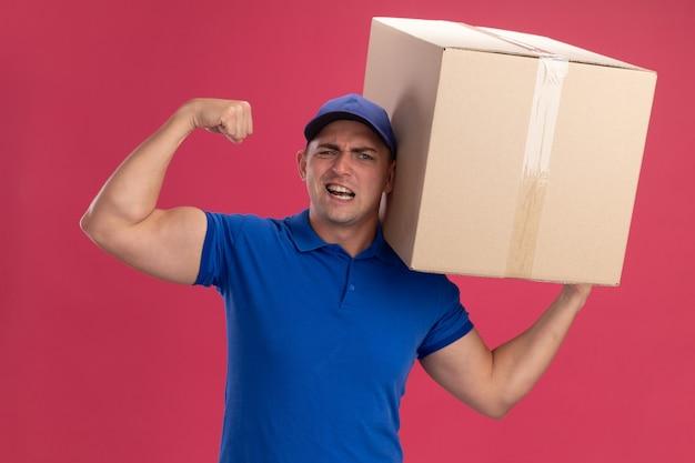 Zelfverzekerde jonge bezorger die uniform met pet draagt die grote doos houdt die sterk gebaar toont dat op roze muur wordt geïsoleerd