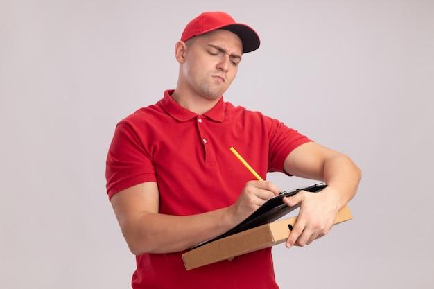 Zelfverzekerde jonge bezorger die uniform met pet draagt die pizzadoos houdt en iets op klembord schrijft dat op witte muur wordt geïsoleerd