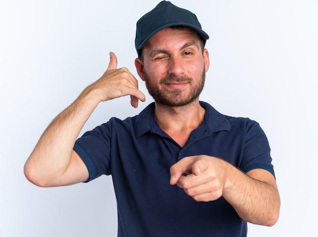 Zelfverzekerde jonge blanke bezorger in blauw uniform en pet kijkend en wijzend op camera die knipoogt en oproepgebaar doet geïsoleerd op een witte muur