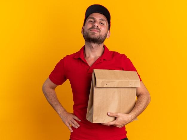 Zelfverzekerde jonge blanke bezorger in rood uniform en pet die hand op taille houdt met papieren pakket kijkend naar camera geïsoleerd op oranje muur