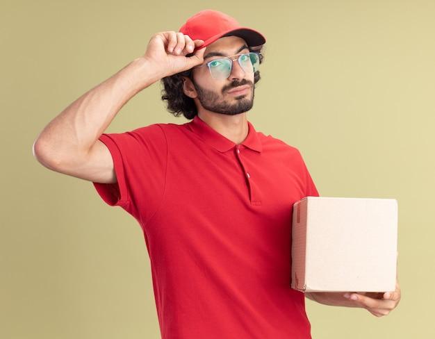 Zelfverzekerde jonge blanke bezorger in rood uniform en pet met bril met cardbox-grijpende dop geïsoleerd op olijfgroene muur