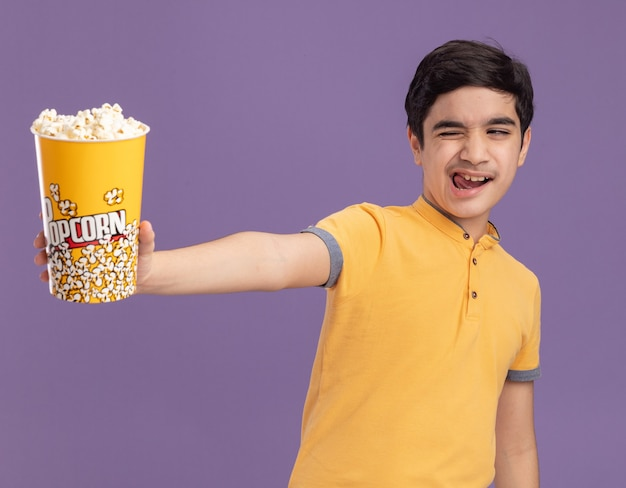 Zelfverzekerde jonge blanke jongen die een emmer popcorn uitrekt en naar de zijkant kijkt die knipoogt en tong laat zien die op een paarse muur is geïsoleerd