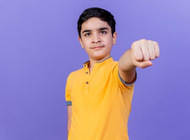 Zelfverzekerde jonge blanke jongen die zich uitstrekt vuist naar geïsoleerd op paarse muur met kopie ruimte