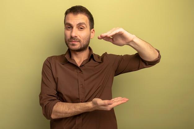 Zelfverzekerde jonge blanke man kijken camera doen grootte gebaar geïsoleerd op olijfgroene achtergrond