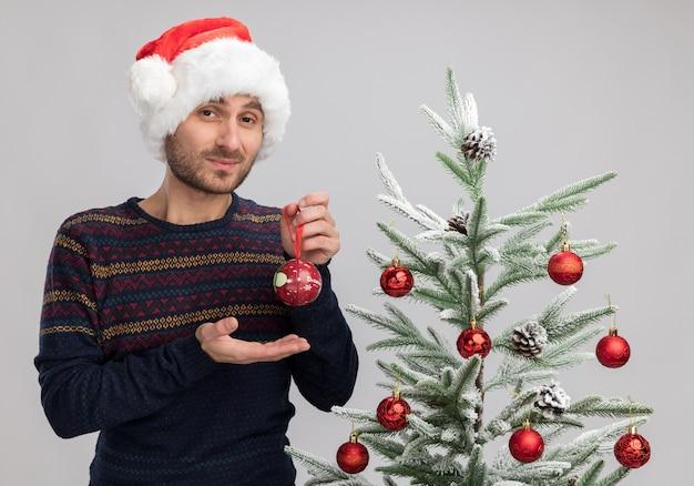 Zelfverzekerde jonge blanke man met kerstmuts staande in de buurt van de kerstboom houden en wijzend met de hand op kerstbal kijken camera geïsoleerd op witte achtergrond