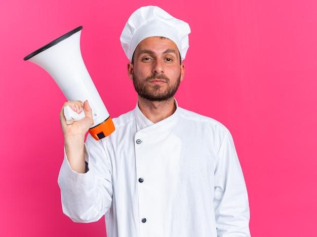 Zelfverzekerde jonge blanke mannelijke kok in chef-kok uniform en pet met spreker