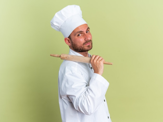 Zelfverzekerde jonge blanke mannelijke kok in chef-kokuniform en pet in profielweergave met deegroller op schouder on