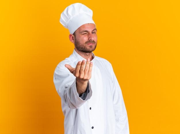 Zelfverzekerde jonge blanke mannelijke kok in uniform van de chef-kok en pet kijkend naar camera knipogend kom hier gebaar geïsoleerd op oranje muur met kopieerruimte
