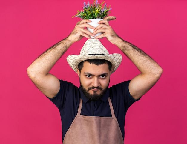 Zelfverzekerde jonge blanke mannelijke tuinman met een tuinhoed met een bloempot boven het hoofd geïsoleerd op een roze muur met kopieerruimte