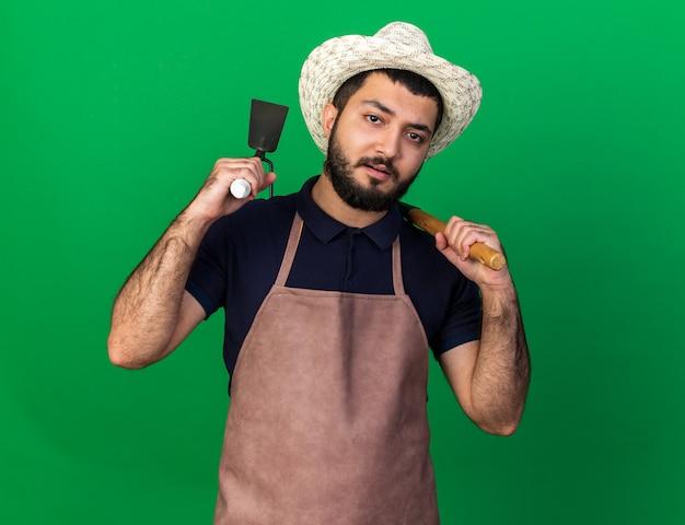 Zelfverzekerde jonge blanke mannelijke tuinman tuinieren hoed bedrijf hark en schoffel hark op schouders geïsoleerd op groene muur met kopie ruimte dragen Gratis Foto