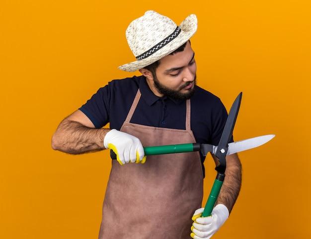 Zelfverzekerde jonge blanke mannelijke tuinman tuinieren hoed en handschoenen dragen en kijken naar tuinieren schaar geïsoleerd op oranje muur met kopie ruimte