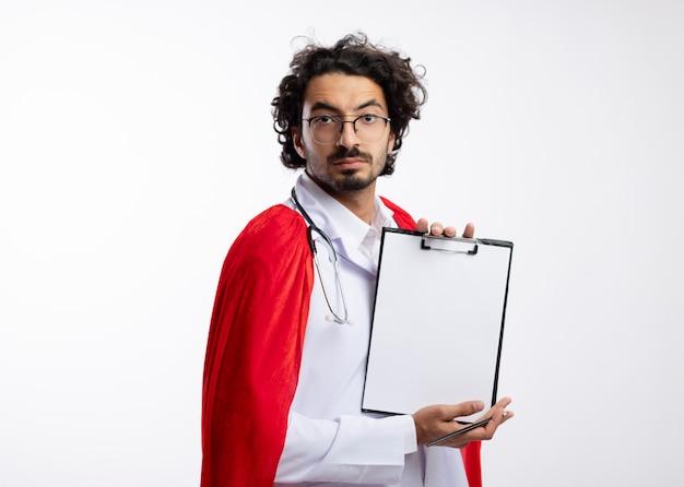 Zelfverzekerde jonge blanke superheld man in optische bril dragen arts uniform met rode mantel en met een stethoscoop om de nek met klembord en potlood geïsoleerd op een witte muur