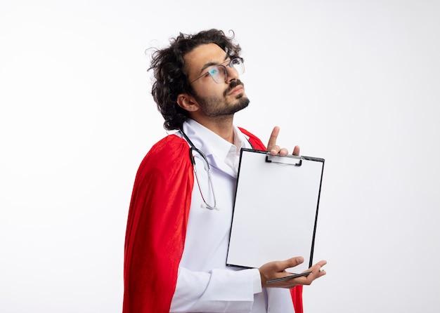 Zelfverzekerde jonge blanke superheld man in optische bril dragen arts uniform met rode mantel en met een stethoscoop om de nek staat zijwaarts met klembord geïsoleerd op een witte muur