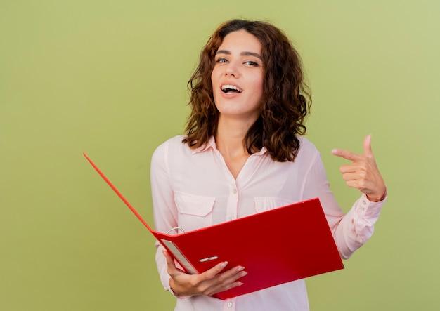 Zelfverzekerde jonge blanke vrouw houdt en wijst op bestandsmap geïsoleerd op groene achtergrond met kopie ruimte