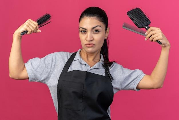 Zelfverzekerde jonge blanke vrouwelijke kapper die uniform draagt en naar voren kijkt met kammen die een sterk gebaar doen geïsoleerd op roze muur