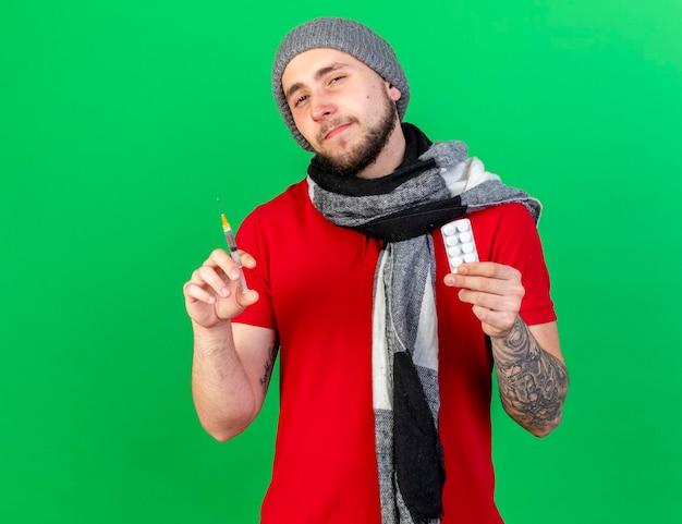 Zelfverzekerde jonge blanke zieke man met winter hoed en sjaal houdt spuit en pakje medische pillen op groen