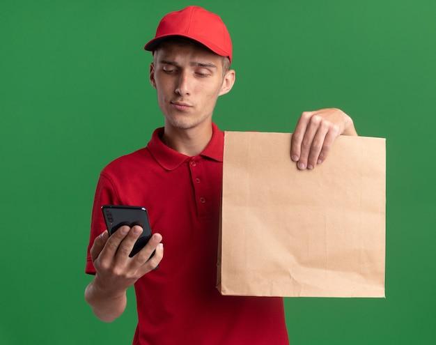 Zelfverzekerde jonge blonde bezorger houdt een papieren pakket vast en kijkt naar de telefoon