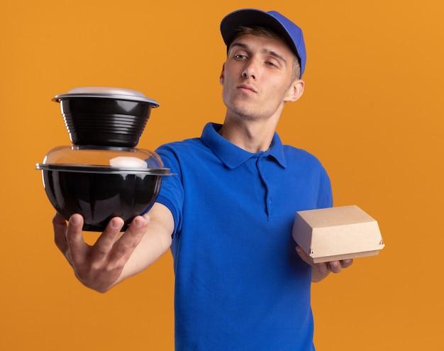 Zelfverzekerde jonge blonde bezorger houdt voedselpakket vast en kijkt naar voedselcontainers