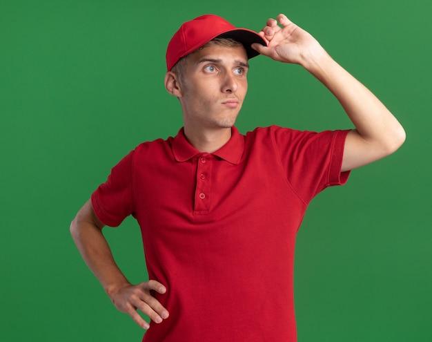 Zelfverzekerde jonge blonde bezorger legt hand op pet en kijkt naar kant geïsoleerd op groene muur met kopieerruimte