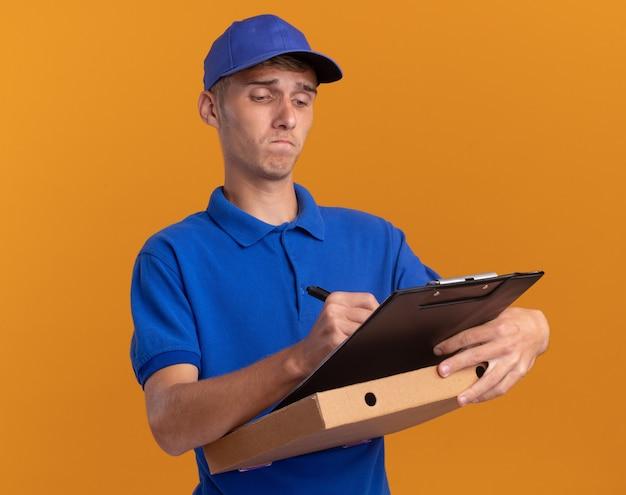Zelfverzekerde jonge blonde bezorger schrijft op klembord met pen die op pizzadoos op sinaasappel houdt