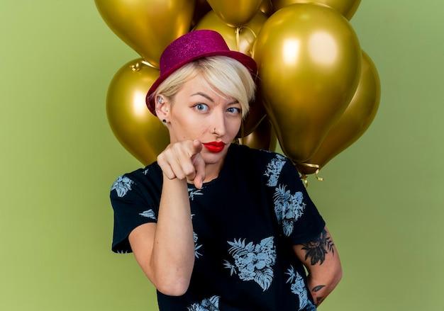 Zelfverzekerde jonge blonde feestvrouw die feestmuts draagt en ballonnen achter haar rug houdt, kijkend en wijzend naar voorzijde geïsoleerd op olijfgroene muur