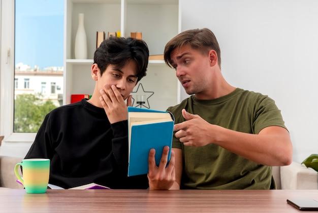 Zelfverzekerde jonge blonde knappe man houden en wijzend op boek aan tafel zitten en kijken naar jonge brunette knappe kerel hand zetten mond kijken boek in woonkamer