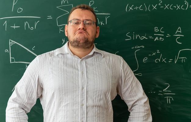 Zelfverzekerde jonge blonde leraar met een bril die voor het bord in de klas staat en de handen op de taille houdt terwijl hij naar de camera kijkt